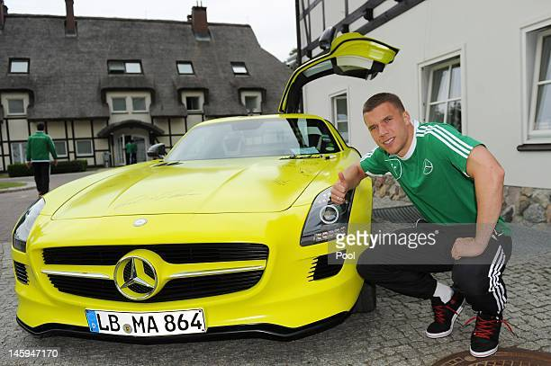 Lukas Podolski of Germany autographs the bonnet of an MercedesBenz SLS AMG ECELL emblazoned with the autographs of the EURO 2012 German national team...