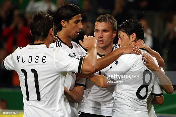 Lukas Podolski of Germany celebrates his team's second goal with team mates Miroslav Klose Sami Khedira and Mesut Oezil during the EURO 2012 Group A...