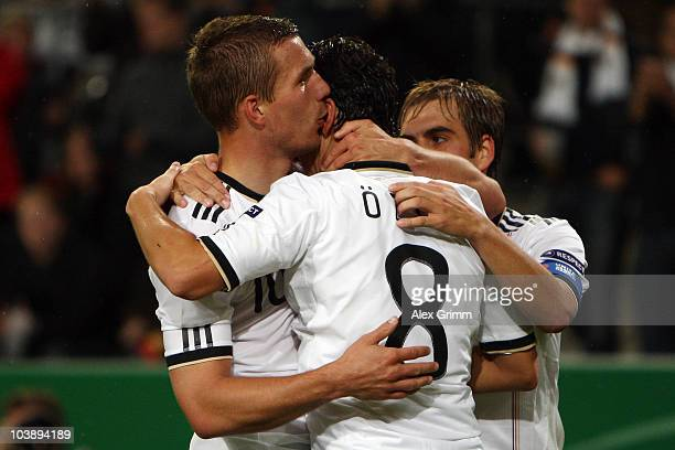 Lukas Podolski of Germany celebrates his team's second goal with team mates Mesut Oezil and Philipp Lahm during the EURO 2012 Group A Qualifier match...