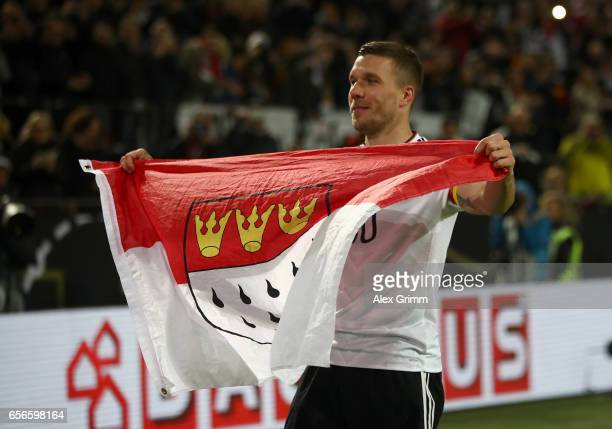 Lukas Podolski of Germany celebrates holding the Koln flag after playing his final game for Germany the international friendly match between Germany...