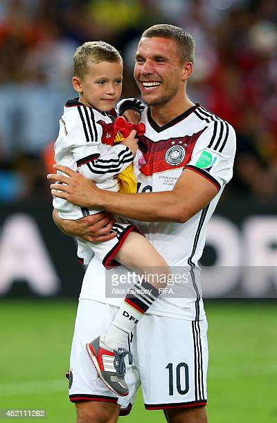 Lukas Podolski of Germany celebrates the win with his son Louis after the 2014 FIFA World Cup Brazil Final match between Germany and Argentina at...