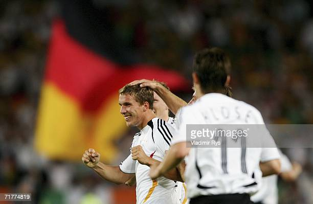 Lukas Podolski of Germany celebrates with his team mates after scoring the first goal during the Euro 2008 qualifying match between Germany and the...
