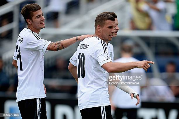 Lukas Podolski of Germany celebrates with teammates after scoring his team's third goal during the International Friendly match between Ecuador and...