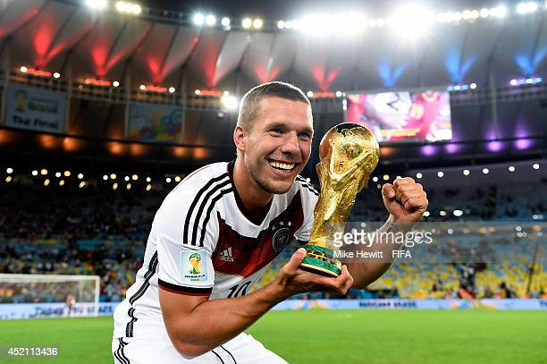 Lukas Podolski of Germany celebrates with the World Cup trophy after the 2014 FIFA World Cup Brazil Final match between Germany and Argentina at...