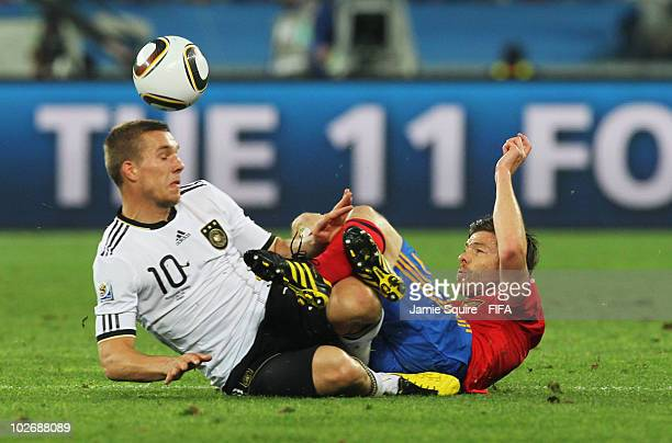 Lukas Podolski of Germany clashes with Xabi Alonso of Spain during the 2010 FIFA World Cup South Africa Semi Final match between Germany and Spain at...