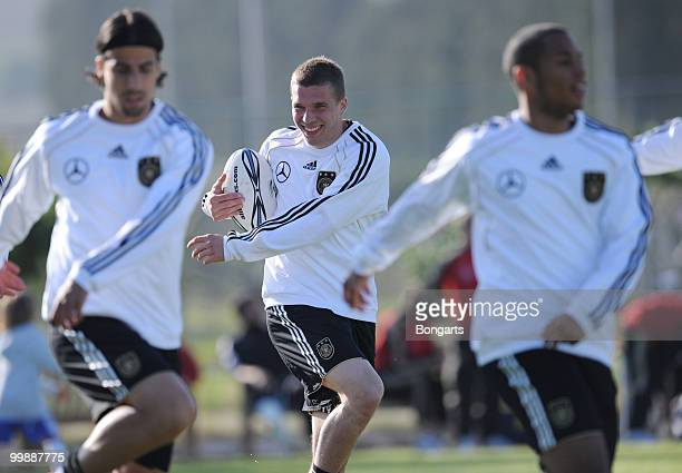 Lukas Podolski of Germany exercises with a rugby ball during a German National Team rugby training session at Verdura Golf Spa Resort on May 18 2010...