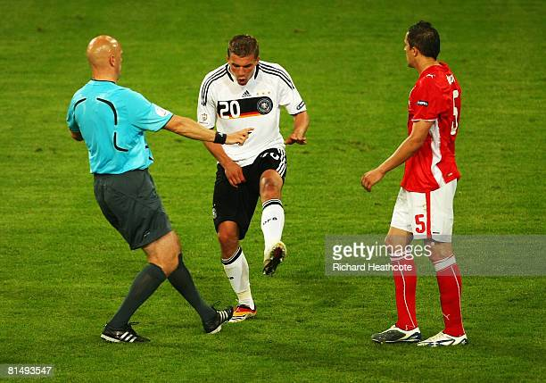 Lukas Podolski of Germany gestures to referee Tom Henning Ovrebo of Norway as Dariusz Dudka of Poland looks on during the UEFA EURO 2008 Group B...