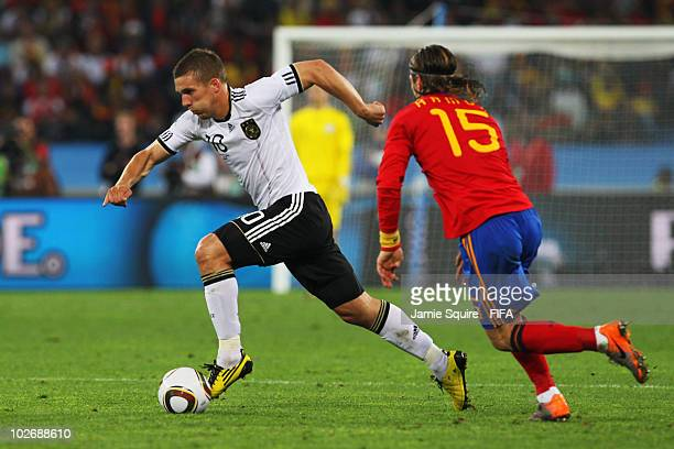 Lukas Podolski of Germany in action against Sergio Ramos of Spain during the 2010 FIFA World Cup South Africa Semi Final match between Germany and...