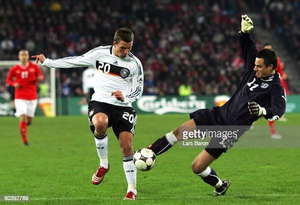 Lukas Podolski of Germany in action with Diego Benaglio of Switzerland prior to the fourth goal scored by Podolski during the international friendly...