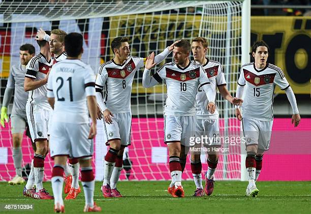 Lukas Podolski of Germany is congratulated by teammates after scoring his team's second goal during the International Friendly match between Germany...