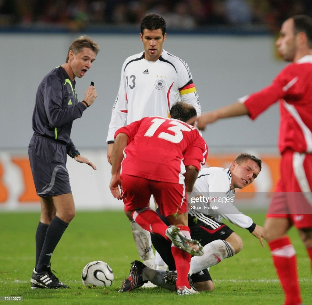 Lukas Podolski of Germany kicks Zurab Khnizanishvili of Georgia for which he is given the red card by referee Gerald Lehner during the friendly match between Germany and Georgia at the Ostsee Stadium on October 7, 2006 in Rostock, Germany