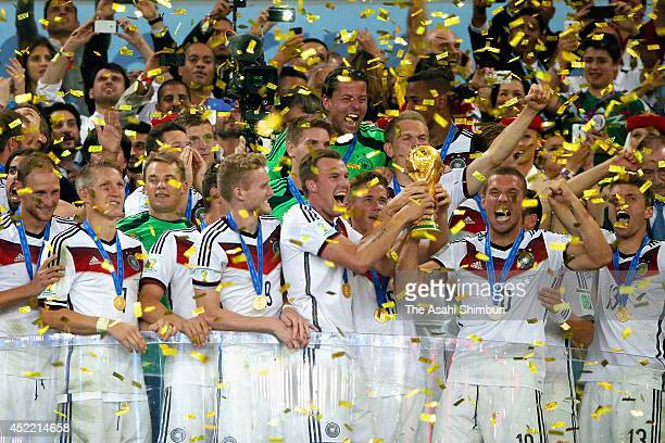 Lukas Podolski of Germany lifts the World Cup trophy during the award ceremony after the 2014 FIFA World Cup Brazil Final match between Germany and...