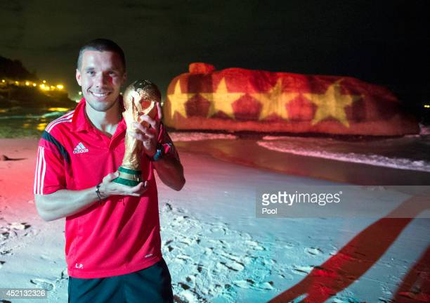 Lukas Podolski of Germany poses with the World Cup trophy in front of a projection displaying 4 world cup winning stars as he celebrates with...