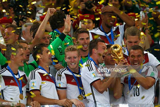 Lukas Podolski of Germany raises the World Cup trophy and celebrates with teammates after defeating Argentina 1-0 in extra time during the 2014 FIFA...