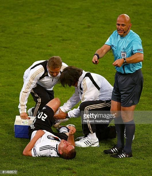 Lukas Podolski of Germany receives medical treatment by doctor Hans-Wilhelm Mueller-Wohlfahrt during the UEFA EURO 2008 Group B match between Germany...