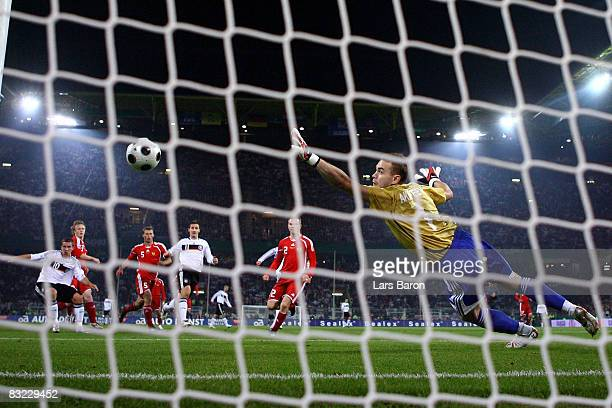 Lukas Podolski of Germany scores the first goal past goalkeeper Igor Akinfeev of Russia during the FIFA 2010 World Cup Group Four Qualifying match...