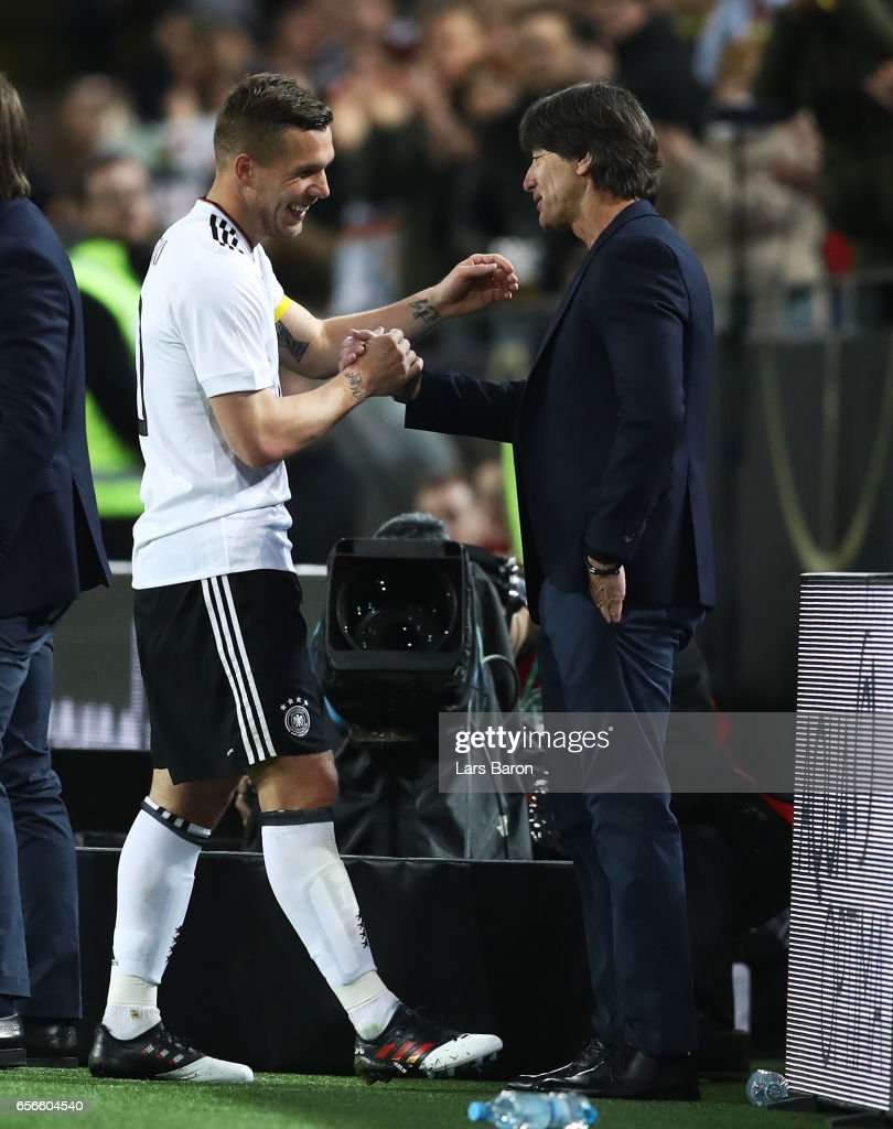 Lukas Podolski of Germany (L) shakes hands with Joachim Loew, manager of Germany (R) as he is subbed during his last international match for Germany during the international friendly match between Germany and England at Signal Iduna Park on March 22, 2017 in Dortmund, Germany.