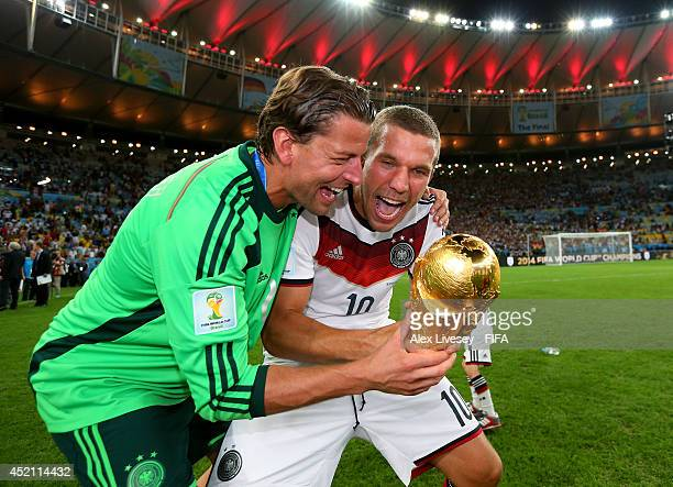 Lukas Podolski of Germany shares a joke with Roman Weidenfeller of Germany while holding the World Cup trophy after the 2014 FIFA World Cup Brazil...