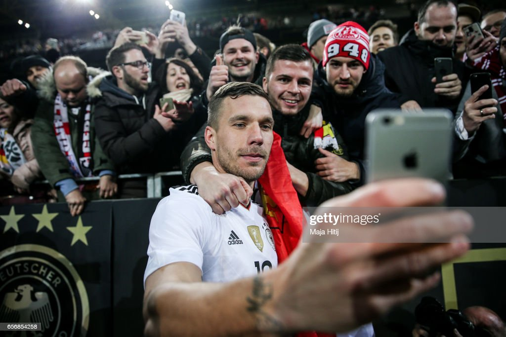 Lukas Podolski of Germany takes a selfie with supporters after playing his final international match for Germany during the international friendly match between Germany and England at Signal Iduna Park on March 22, 2017 in Dortmund, Germany.