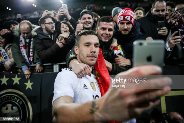 Lukas Podolski of Germany takes a selfie with supporters after playing his final international match for Germany during the international friendly...