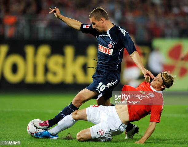Lukas Podolski of Koeln battles for the ball with Eugen Polanski of Mainz during the Bundesliga match between FSV Mainz 05 and 1FC Koeln at Bruchweg...