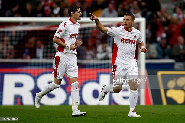 Lukas Podolski of Koeln celebrates his team's first goal with team mate Milivoje Novakovic during the Bundesliga match between 1. FC Koeln and FC...
