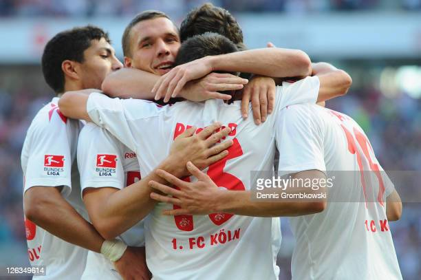 Lukas Podolski of Koeln celebrates with team mates after Mato Jajalo has scored their team's opening goal during the Bundesliga match between 1. FC...