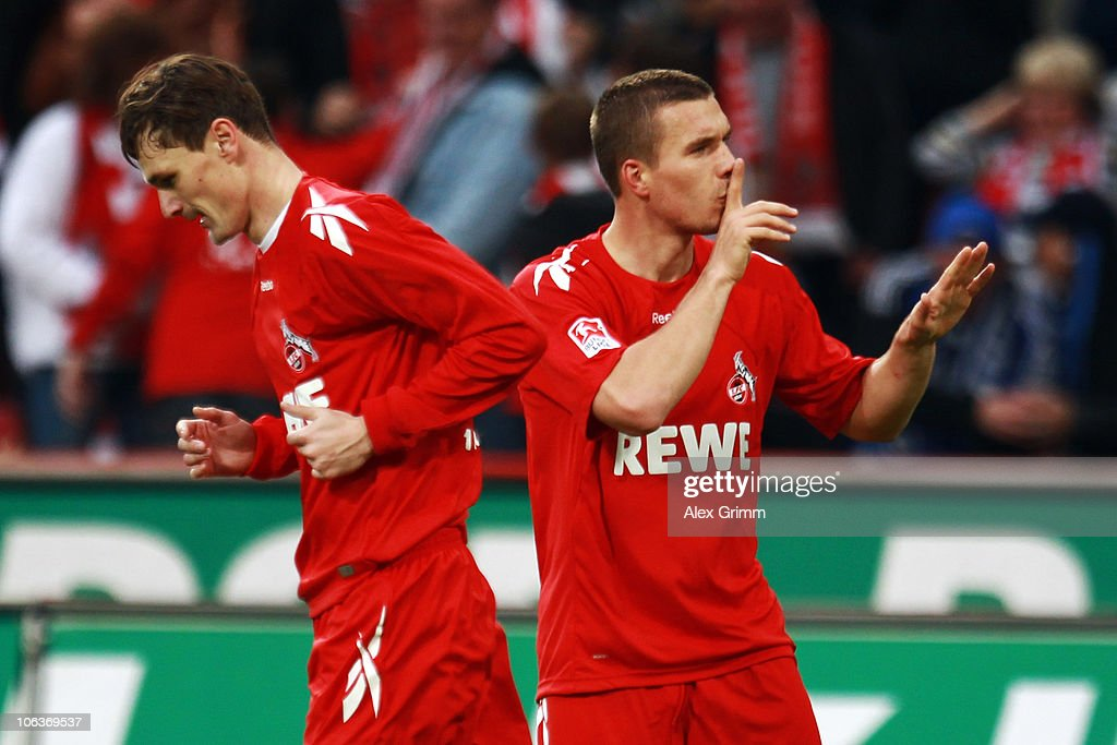 Lukas Podolski (R) of Koeln gestures to the supporters after team mate Milivoje Novakovic scored his team's second goal during the Bundesliga match between 1 FC Koeln and Hamburger SV at the RheinEnergieStadion on October 30, 2010 in Cologne, Germany.