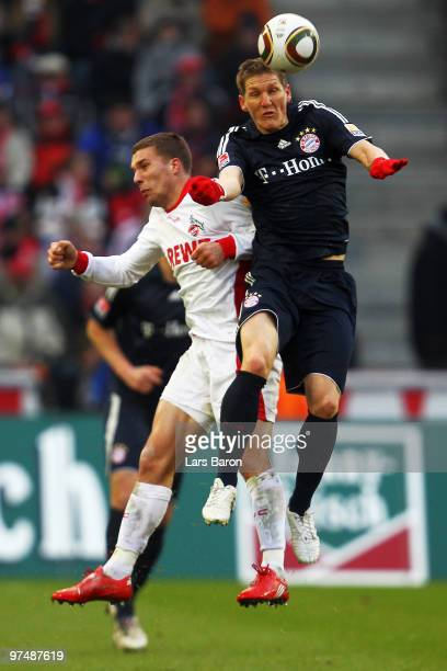 Lukas Podolski of Koeln goes up for a header with Bastian Schweinsteiger of Muenchen during the Bundesliga match between 1 FC Koeln and FC Bayern...