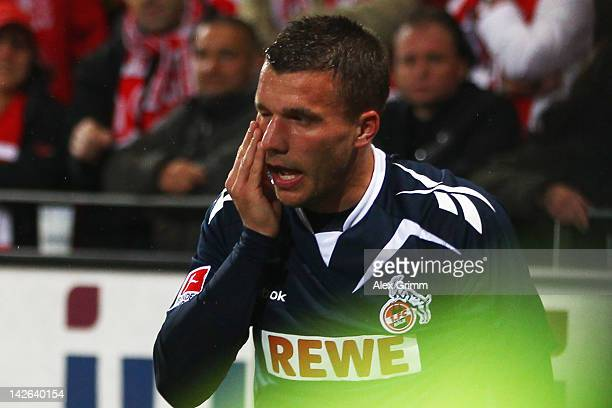 Lukas Podolski of Koeln reacts after being hit by a coin during the Bundesliga match between between FSV Mainz 05 and 1 FC Koeln at Coface Arena on...