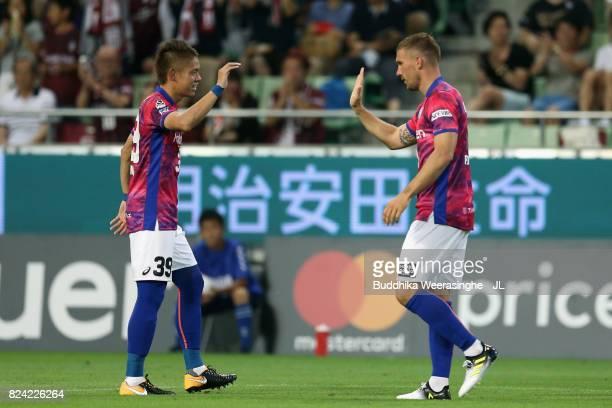 Lukas Podolski of Vissel Kobe celebrates scoring the opening goal with his team mate Masahiko Inoha during the JLeague J1 match between Vissel Kobe...