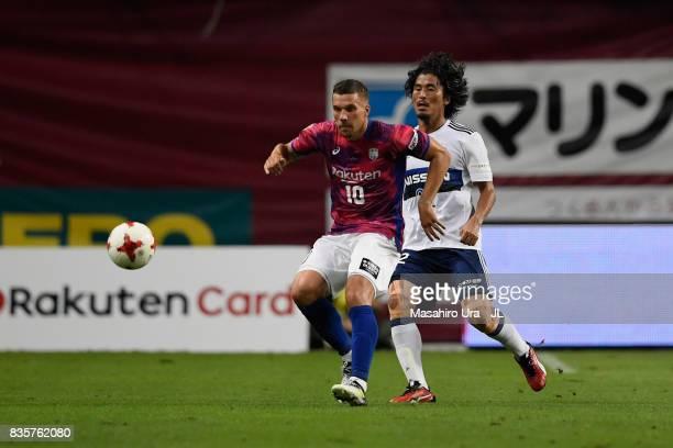 Lukas Podolski of Vissel Kobe controls the ball under pressure of Yuji Nakazawa of Yokohama FMarinos during the JLeague match between Vissel Kobe and...