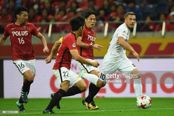 Lukas Podolski of Vissel Kobe controls the ball under pressure of Ryota Moriwaki and Yuki Abe of Urawa Red Diamonds during the JLeague J1 match...