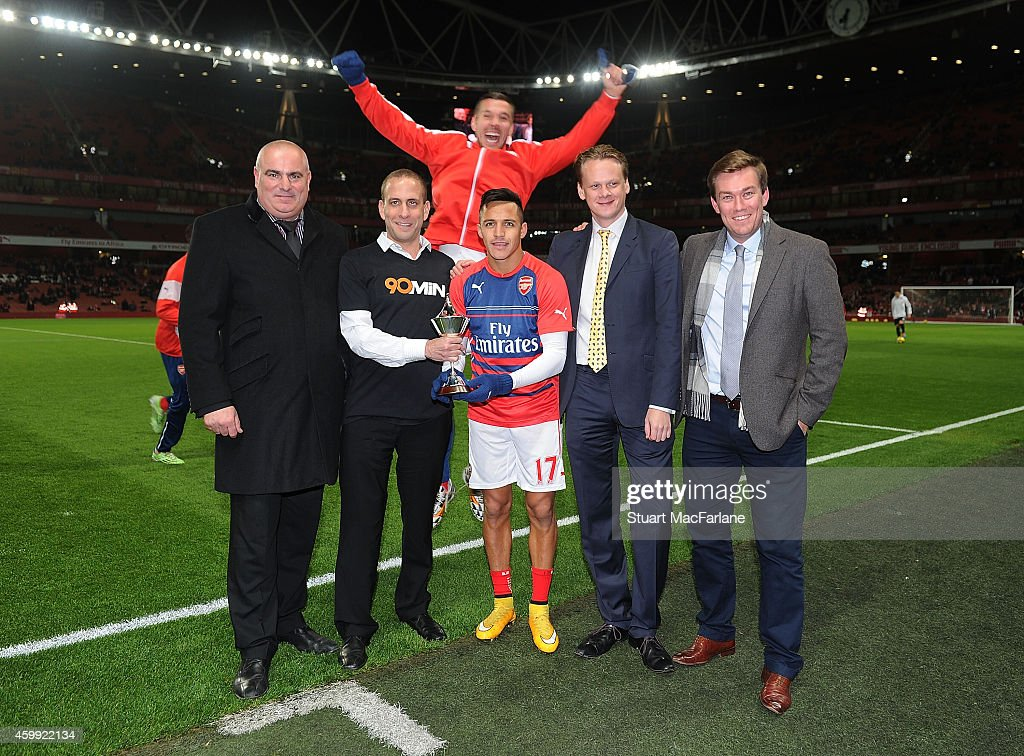 Lukas Podolski photobombs the Alexis Sanchez PFA Fans Player Of The Month presentation before the Barclays Premier League match between Arsenal and Southampton at Emirates Stadium on December 3, 2014 in London, England.