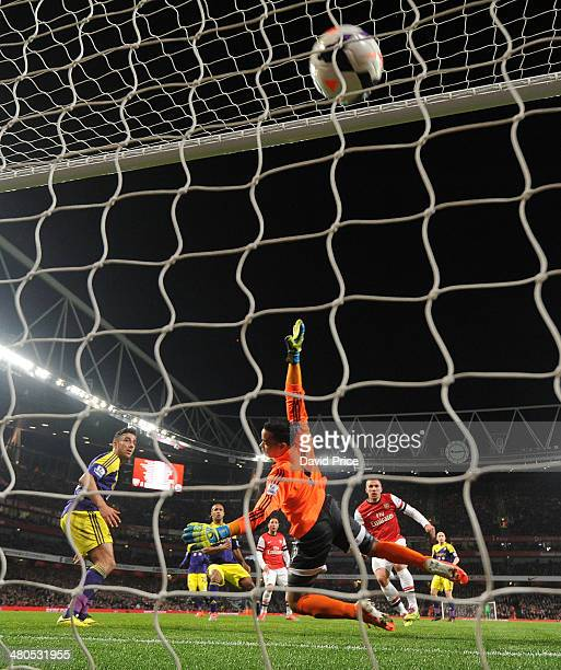Lukas Podolski scores Arsenal's 1st goal past Michel Vorm of Swansea during the match between Arsenal and Swansea City in the Barclays Premier League...