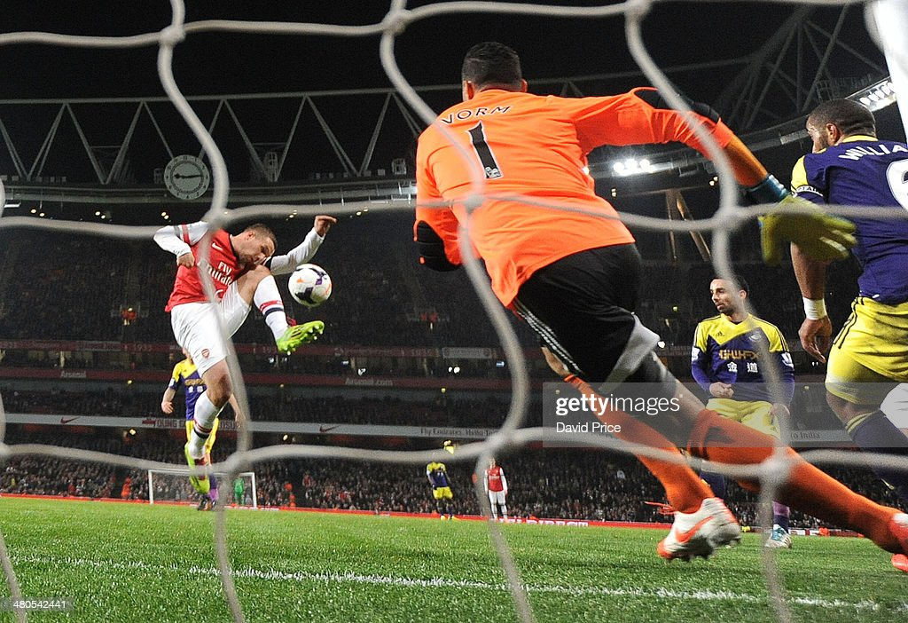 Lukas Podolski scores Arsenal's 1st goal past Michel Vorm of Swansea during the match between Arsenal and Swansea City in the Barclays Premier League at Emirates Stadium on March 25, 2014 in London, England.