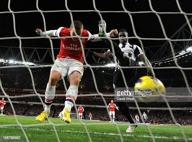 Lukas Podolski scores Arsenal's 3rd goal as Cheick Tiote of Newcastle trys to clear the ball during the Barclays Premier League match between Arsenal...