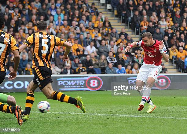 Lukas Podolski scores Arsenal's 3rd goal his 2nd as James Chester of Hull closes in during the match between Hull City and Arsenal in the Barclays...