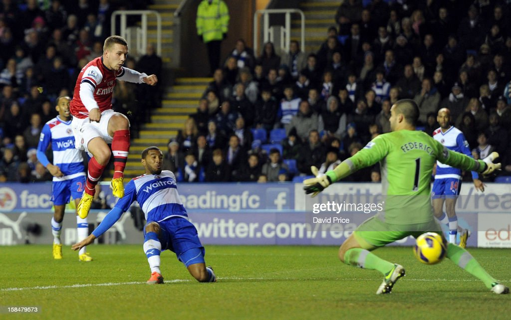 Lukas Podolski scores Arsenal's first goal past Adam Federici as Adrian Mariappa of Reading closes in during the Barclays Premier League match between Reading and Arsenal at Madejski Stadium on December 17, 2012 in Reading, England.