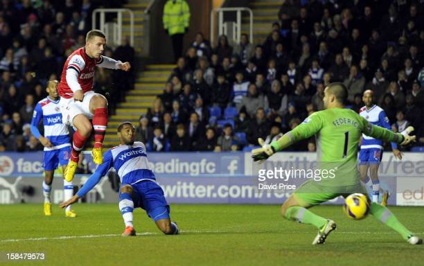 Lukas Podolski scores Arsenal's first goal past Adam Federici as Adrian Mariappa of Reading closes in during the Barclays Premier League match...