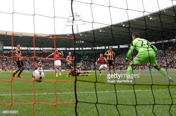 Lukas Podolski shoots past Hull goalkeeper Stephen Harper to score the 2nd Arsenal goal during the Barclays Premier League match between Hull City...