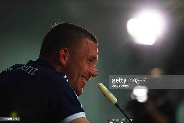 Lukas Podolski smiles during a Germany press conference ahead of their FIFA 2014 World Cup group C qualifying match against Ireland at...