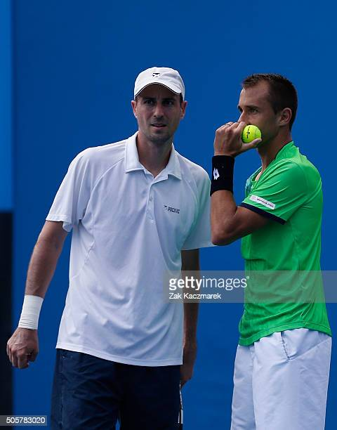 Lukas Rosol of the Czech Republic and Igor Zelenay of Slovakia talk tactics in their first round match against Steve Johnson of the United States and...