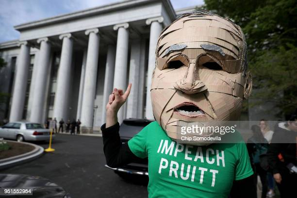 Lukas Ross of Friends of the Earth wears a giant mask of Environmental Protection Agency Administrator Scott Pruitt while protesting outside the...
