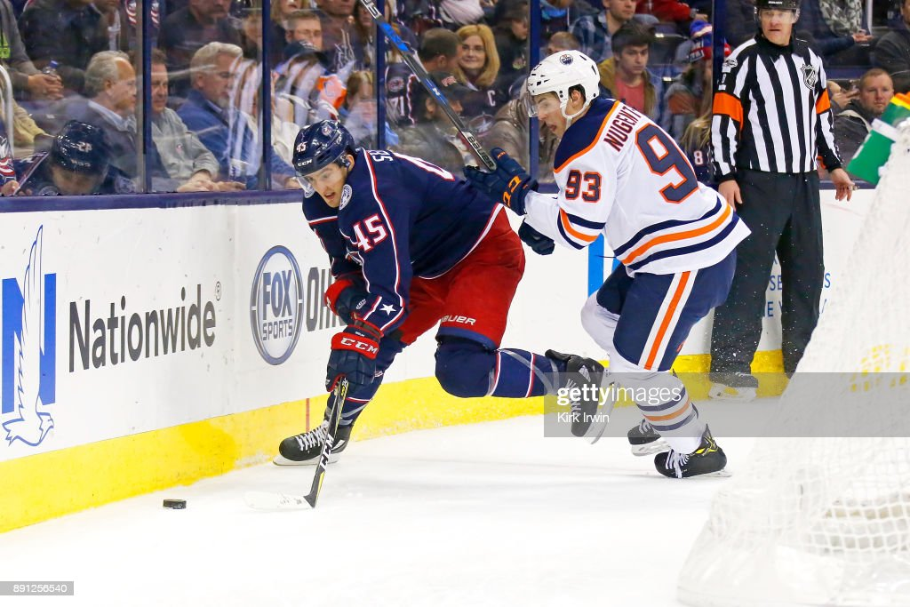Lukas Sedlak #45 of the Columbus Blue Jackets and Ryan Nugent-Hopkins #93 of the Edmonton Oilers battle for control of the puck during the second period on December 12, 2017 at Nationwide Arena in Columbus, Ohio.