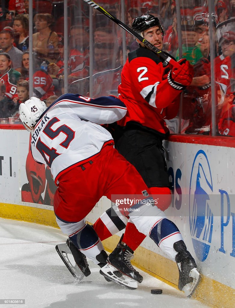 Lukas Sedlak #45 of the Columbus Blue Jackets checks John Moore #2 of the New Jersey Devils during the first period on February 20, 2018 at Prudential Center in Newark, New Jersey.