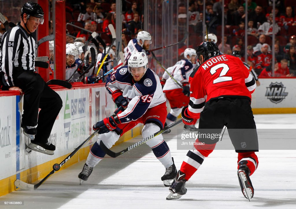 Lukas Sedlak #45 of the Columbus Blue Jackets plays the puck against John Moore #2 of the New Jersey Devils on February 20, 2018 at Prudential Center in Newark, New Jersey.