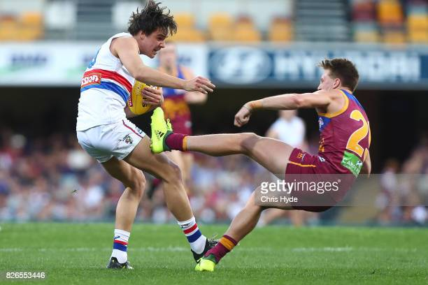 Lukas Webb of the Bulldogs is tackled by Alex Witherden of the Lions during the round 20 AFL match between the Brisbane Lions and the Western...