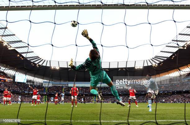 Lukasz Fabianski of Arsenal makes a save from Emmanuel Adebayor of Manchester City during the Barclays Premier League match between Manchester City...