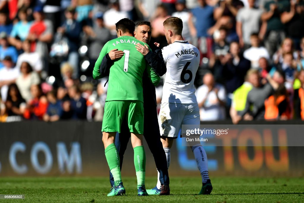 Lukasz Fabianski of Swansea City is embraced by Carlos Carvalhal, Manaager of Swansea City after the Premier League match between Swansea City and Stoke City at Liberty Stadium on May 13, 2018 in Swansea, Wales.